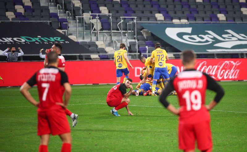 שחקני בני סכנין צופים בשחקני מכבי ת״א חוגגים את שער הניצחון בדקה ה-95